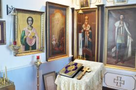 A 19th Century book of gospels is seen in the foreground as icons precious to the church and congregation hang on the wall and iconostasis, which separates the altar from the Holy of Hollies at Holy Assumption of the Virgin Mary Russian Orthodox Church in Kenai.