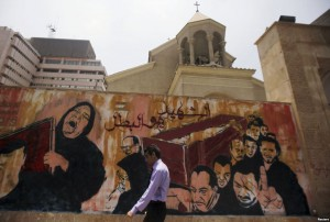 "A man walks past graffiti depicting a funeral outside a church near Cairo's Tahrir Square on Thursday. The graffiti reads ""Martyr or hero"". Photo: CNS/Amr Abdallah Dalsh, Reuters"