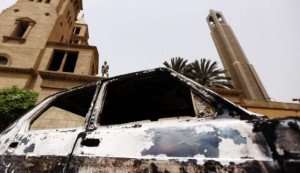 A car burnt in clashes between Muslims and Coptic Christians in April lies in front of Cairo's main Coptic Cathedral. Photo by Reuters