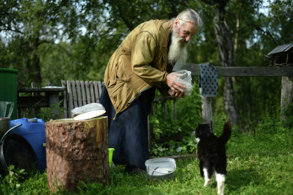 Priest feeding a cat on the Solovetsky Island in the Arkhangelsk Region.