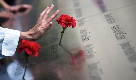 A woman touches a carnation left on a name inscribed into the North Pool during 9/11 memorial ceremonies marking the 12th anniversary of the Sept. 11, 2001, terrorist attacks on the World Trade Center in New York. The attacks claimed the lives of nearly 3,000 people in New York City, Shanksville, Pa., and at the Pentagon.(CNS photo/Adrees Latif, Reuters)