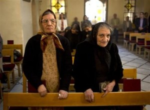 In this photograph made on Sunday, Oct. 27, 2013, women stand during a service in an Armenian Orthodox church in Damascus, Syria. Attacks on Christian districts of the capitals and on Christian villages elsewhere have fueled fears among Syria's religious minorities about the growing role of Islamic extremists among the armed rebels fighting against President Bashar Assad's rule. ((AP Photo/Dusan Vranic))