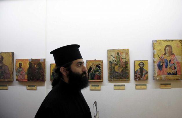 A man use his mobile to take a photo of the 14th century icon of the Virgin Mary, or Panayia, the Merciful after returned looted icons at the Byzantine Museum in capital Nicosia, Cyprus, Tuesday, Nov. 12, 2013.