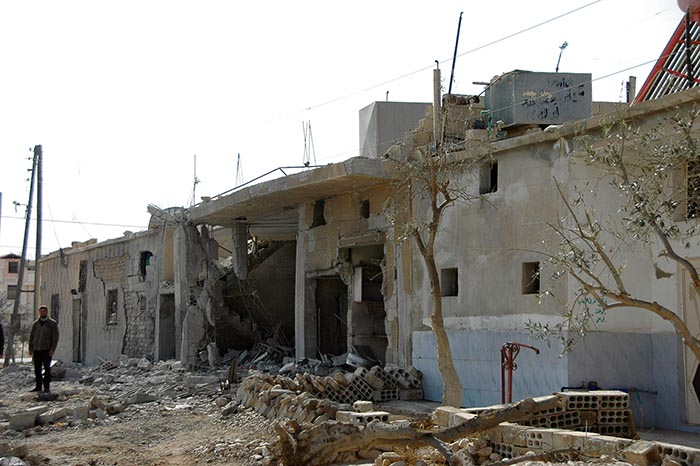Aftermath: a man stands next to ruined homes in Sadad after government forces took control of it from rebel fighters.
