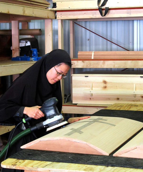 Getting buff: Mother Paraskeva puts a finish on a handmade casket, one of several fundraising items produced by the monastery. (Judith van Vliet)