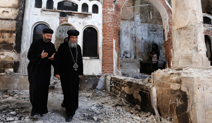 August 26, 2013: Bishop-General Macarius (right), a Coptic Orthodox leader, walks around the damaged Evangelical Church in Minya, south of Cairo. | (REUTERS/Louafi Larbi)