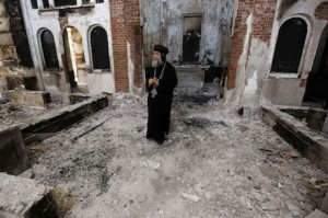 A Coptic Orthodox bishop surveys a damaged church in Minya, Egypt last year (CNS)