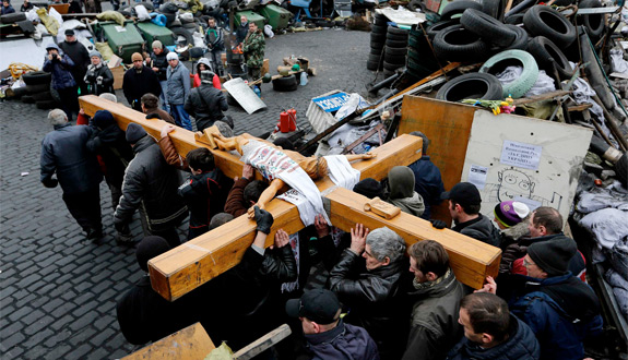 Mourners carry a large wooden crucifix past a barricade during a memorial procession in Independence Square in Kiev, Ukraine, Feb. 25. Dozens of protesters have been killed since November. (CNS photo/Yannis Behrakisi, Reuters)