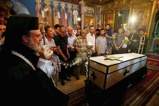 People pray over casket of Palestinian Christian woman who doctors said was killed in an Israeli air strike. Reuters/Suhaib Salem