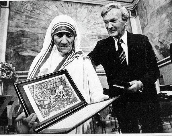 "© AP Photo. Mother Teresa (L), with Chairman of the Norwegian Nobel Committee, John Sanness, during the award ceremony in Oslo on December 10, 1979. Behind them is the famous wall painting ""Sun Rise"" by Edvard Munch"