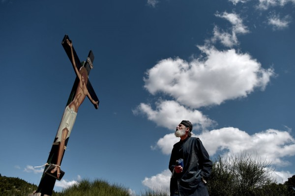 A monk of the Greek Orthodox Church looks at an image of Jesus crucified, during the ceremony marking the Apokathelosis, the removal of Christ's dead body from the Cross, which forms a key part of Orthodox Easter, at the Church of the Dormition of the Virgin in Penteli, north Athens on April 10, 2015.
