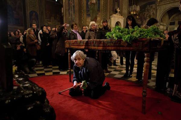 A Christian passes under a table on which a Bible is placed during the Good Friday service in the eastern-orthodox golden-domed Alexander Nevski cathedral in Sofia. April 10, 2015.
