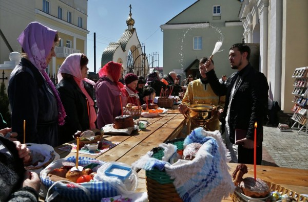 An Orthodox priest blesses traditional Easter cakes and painted eggs in preparation for an Easter celebration at a church in the town of Novogrudok, 150 kilometers (93 miles) west of the capital Minsk, Belarus. Saturday, April 11, 2015.