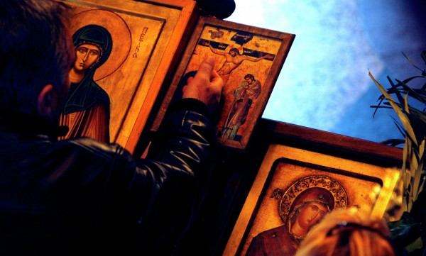 A man touches an icon with the crucifixion of Jesus Christ on Good Friday at St. Petka Orthodox church in Skopje, Macedonia. April 10, 2015.