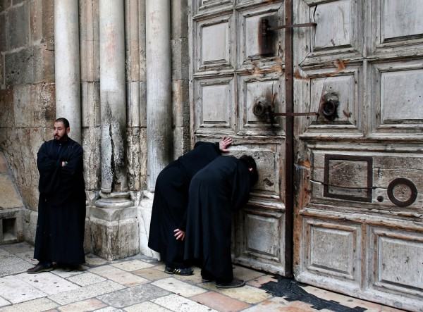 Christian Orthodox priests look through a hole in the main door of the Church of the Holy Sepulchre, before the Holy Fire ceremony around Jesus' tomb, in Jerusalem's Old City. April 11, 2015.
