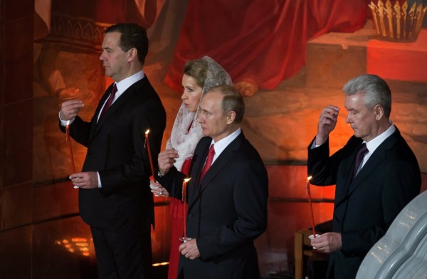 Russian President Vladimir Putin (C), Prime Minister Dmitry Medvedev (L), his wife Svetlana (second from the left), and Mayor Sergei Sobyanin (R) cross themselves during the Easter service in Christ the Savior Cathedral in Moscow, Russia. April 12, 2015.
