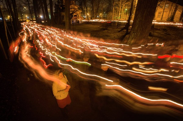 In this photo taken with long time exposure, Orthodox believers walk with candles during Easter midnight mass at a church in St. Petersburg, Russia. April 12, 2015.