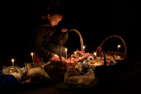 A Kyrgyz Orthodox worshiper lights candles as she celebrates Orthodox Easter during a midnight mass at a church in Bishkek. April 12, 2014.