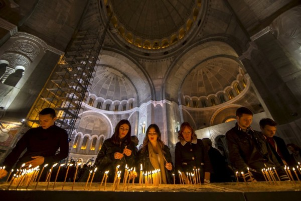 Worshippers light candles in the St. Sava temple during an Orthodox Easter service in Belgrade. April 11, 2015.