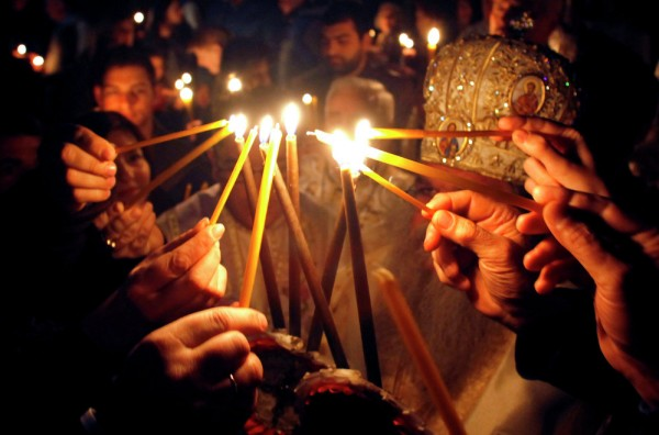 Worshippers light candles to participate in a procession at St. Clement Christian Orthodox church in Macedonia's capital Skopje, during Easter service. April 12, 2015.
