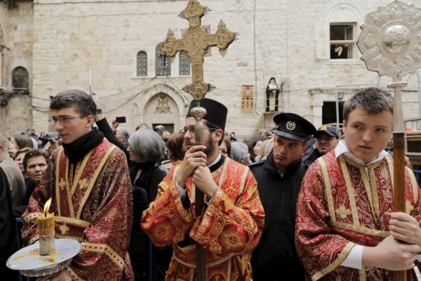 PHOTO: REUTERS/AMMAR AWAD. Members of the Greek Orthodox clergy await the arrival of the Greek Orthodox Patriarch of Jerusalem Metropolitan Theophilos before the washing of the feet ceremony outside the Church of the Holy Sepulchre in Jerusalem's Old City, April 9, 2015, ahead of Orthodox Easter.