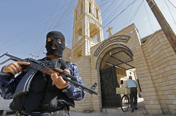 An Iraqi security officer, stands guard outside the Church of the Virgin Mary in Mosul in 2012