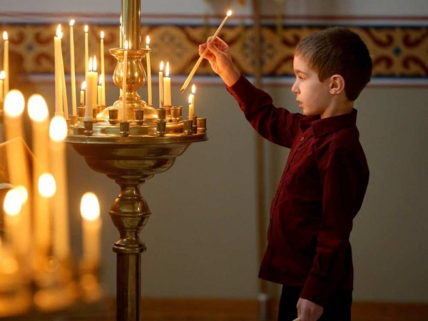 A young boy lights a candle for the living and the dead as a means of paying homage to both at the front of the church upon entering. Christ the Saviour Orthodox Church held their Christmas service. JULIE OLIVER / OTTAWA CITIZEN