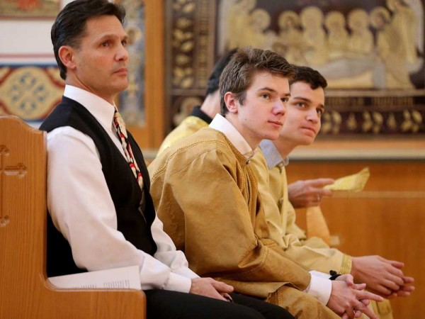 Altar boy Nicholas La Libertie (centre) sits with other church members at the front while listening to the service. JULIE OLIVER / OTTAWA CITIZEN