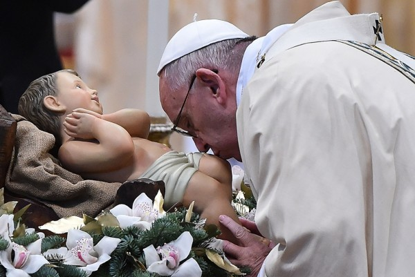Pope Francis kisses a statue of Baby Jesus during the Epiphany mass at St Peter's Basilica in the Vatican Gabriel Bouys/AFP