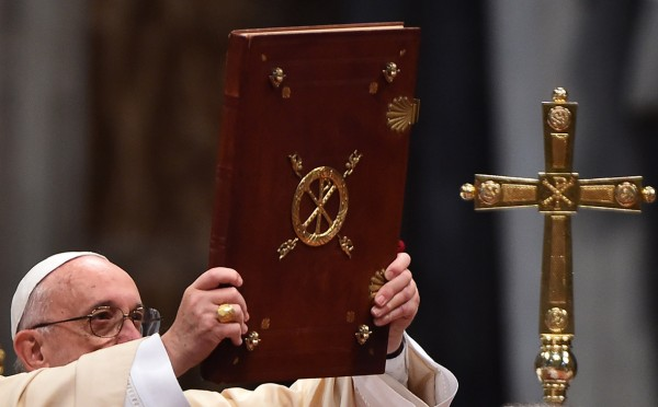 Pope Francis holds the book of the Gospels during the Epiphany mass Gabriel Bouys/AFP