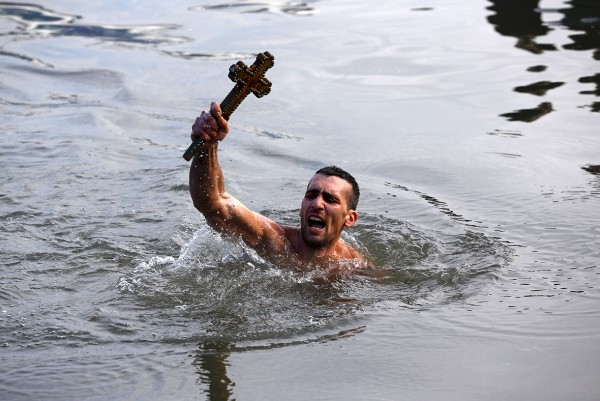 Nikolas Solis, 28, holds a wooden crucifix after retrieving it from the Golden Horn in Istanbul Murad Sezer/Reuters