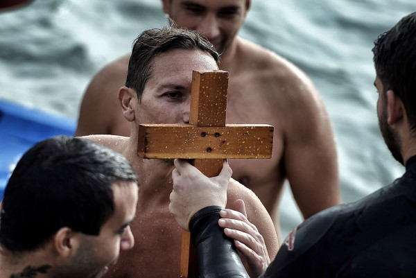 A swimmer kisses a wooden cross after retrieving it from the sea on Epiphany Day in a southern suburb of Athens, Greece Aris Messinis/AFP