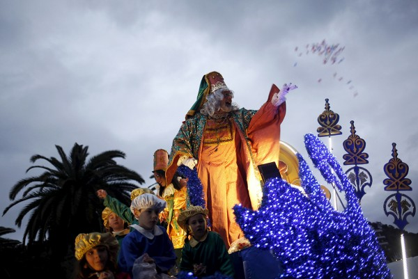 An actor dressed as Melchior, one of the Three Wise Men, throws sweets to children in Malaga, southern Spain Jon Nazca/Reuters