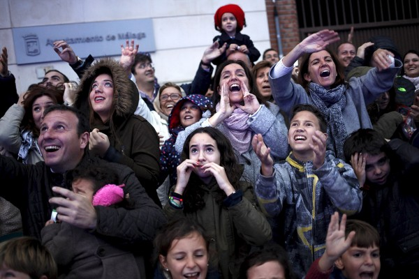 People react as sweets are thrown to them from a float by actors dressed as the Three Wise Men during the traditional Epiphany parade in Malaga, southern Spain Jon Nazca/Reuters
