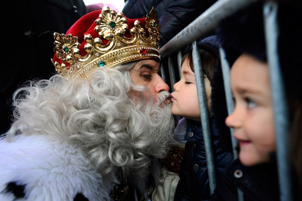 A man dressed as one of the Three Wise Men kisses a child in Gijon. Children in Spain traditionally receive their Christmas presents delivered by the Three Wise Men on the morning of 6 January, during the Epiphany loy Alonso/Reuters