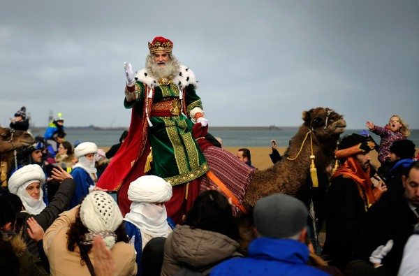A man dressed as one of the Three Wise Men greets children upon arriving at Poniente beach in Gijon, Spain Eloy Alonso/Reuters