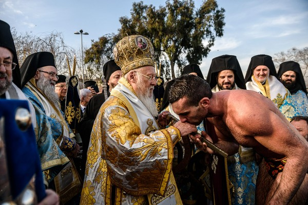 Nicolaos Solis kisses the hand of Greek Orthodox Ecumenical Patriarch Bartholomew near the Bosphorus river's Golden Horn in Istanbul Ozan Kose/AFP