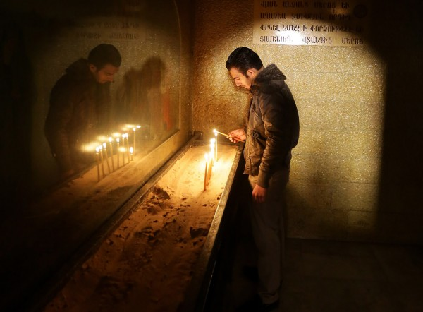 A man lights a candle during Armenian Orthodox Christmas celebrations at the Saint Sarkis Church in Damascus, Syria Louai Beshara/AFP
