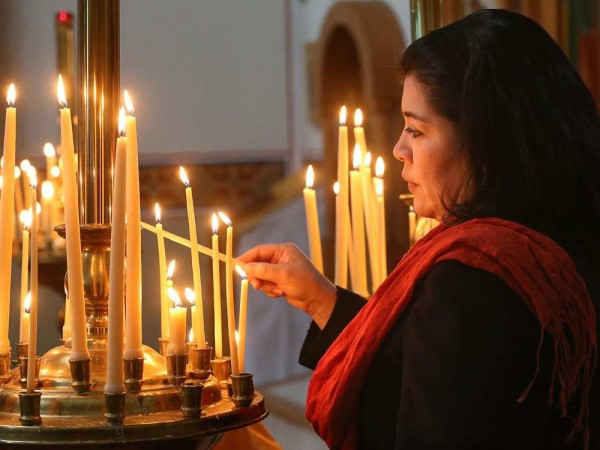 Parishioner Marta Santanilla lights a candle for the living in front of the church altar. JULIE OLIVER / OTTAWA CITIZEN