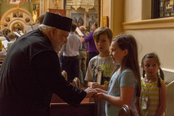 Bishop Paul meeting with some of the children attending St. Mary's vacation bible school who sang with symposium participants