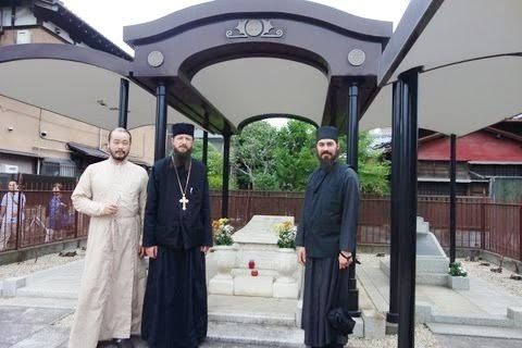 Deacon Iliya Toru with Archimandrite Sergius and Hierodeacon Maximus at the grave of St. Nicholas of Japan in Tokyo's Yanaka Cemetery.