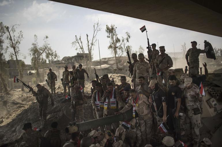 Iraqi Army soldiers gather to celebrate their gains as their fight against Islamic State militants continues in the Old City of Mosul, Iraq, Sunday, July 9, 2017. (AP Photo/Felipe Dana)