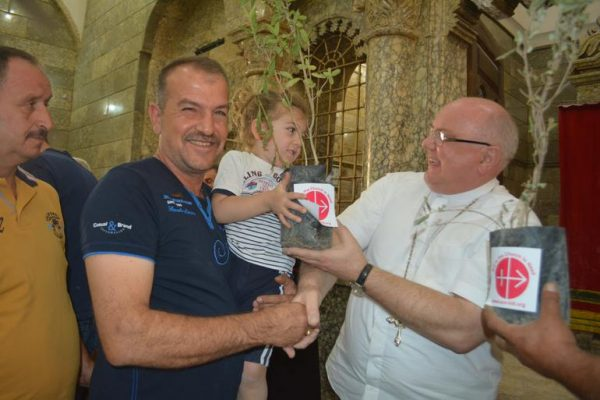 Aid to the Church in Need Middle East projects' coordinator Father Andrzej Halemba distributes olive tree to a Christian family at St George's Church, Bartela